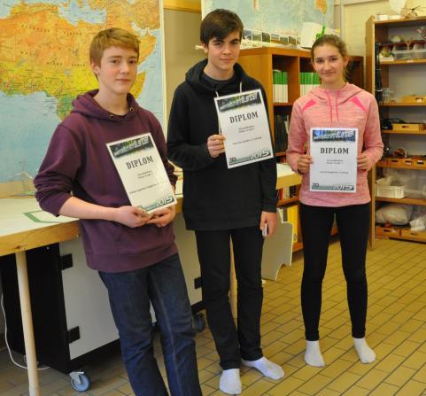 Niklas, Marcus och Astrid visar upp diplomen från tävlingen Teknikåttan.