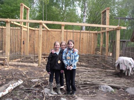 Tre vikingatjejer som vilar ut efter husbygget.