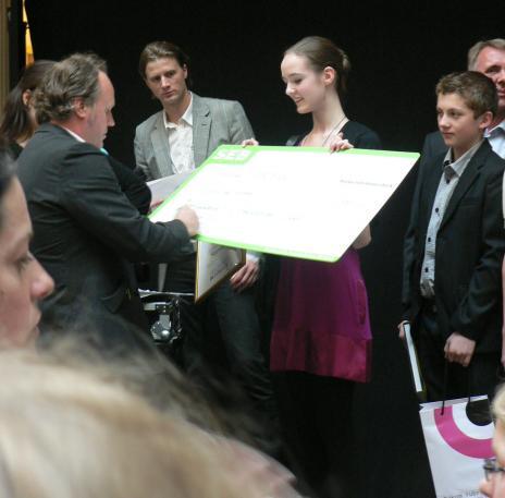 Här ser ni glada Linnea med checken och Bakom rubrikernas Erik Sjögren som signerar den.